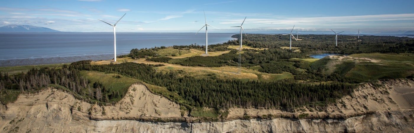 aerial of wind farm turbines against landscape