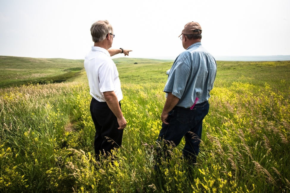 two men talking in field