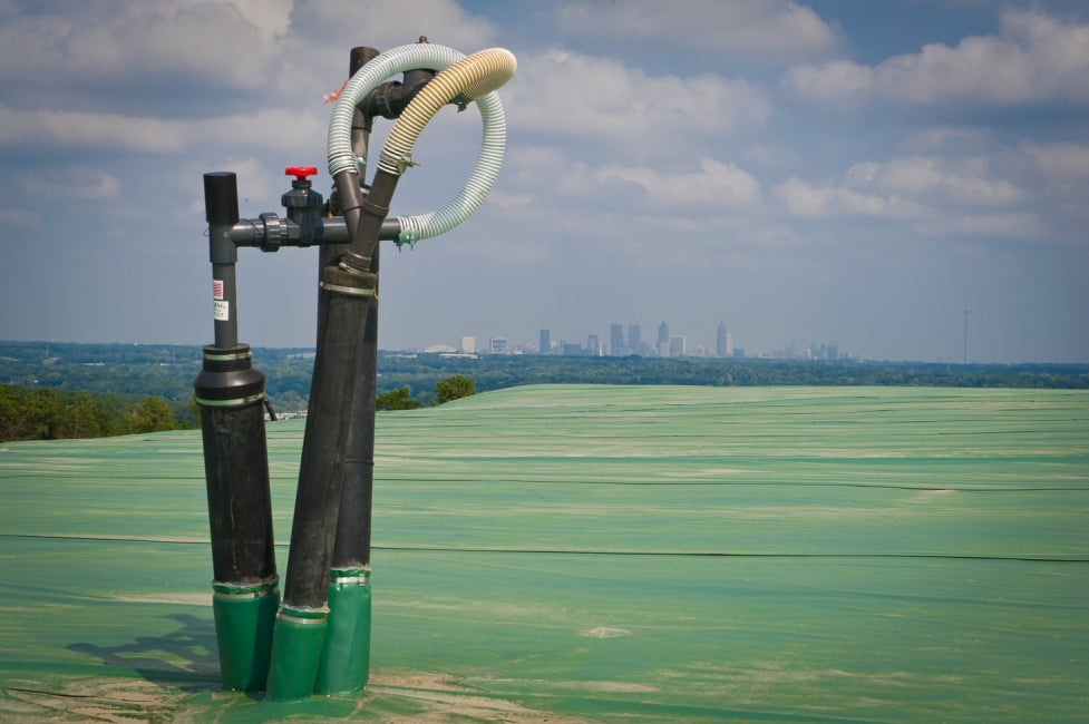 valves in foreground with city skyline on the horizon
