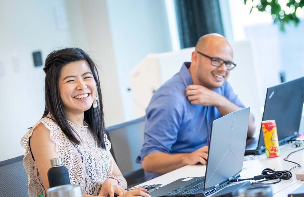 woman and man smiling in front of laptops in a meeting