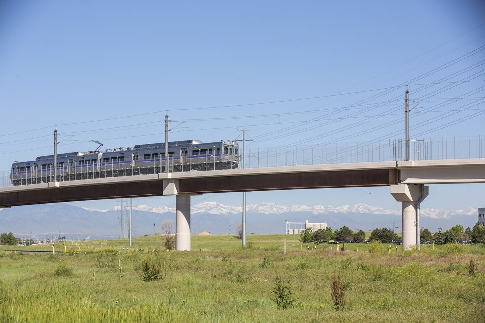 A University of Colorado A Line train traverses the I-70 flyover bridge, close t