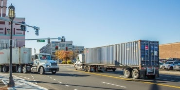 Trucks turning on roadway with intermodal containers