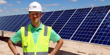 Will Kirby Standing by Solar Installation