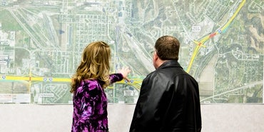 people reviewing a map on a wall